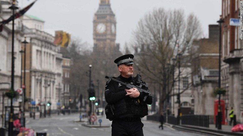 An armed police officer patrols by a security cordon set up along Whitehall by the Houses of Parliament on March 23.