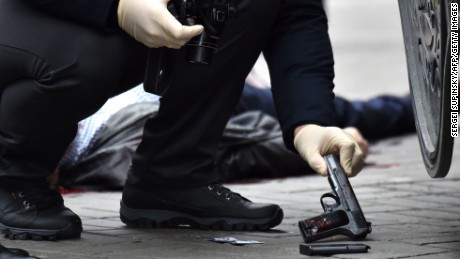 EDITORS NOTE: Graphic content / An Ukrainian police expert seizes a gun at the scene where former Russian MP Denis Voronenkov was shot dead on March 23, 2017 in the center of Kiev.