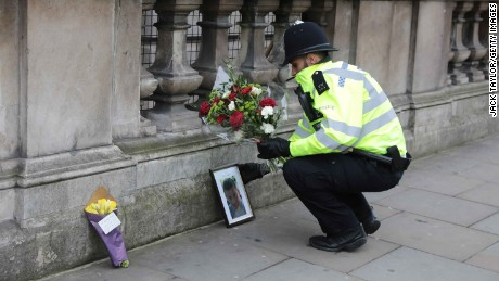LONDON, ENGLAND - MARCH 23: A police officer lays a floral tribute given by a member of the public beside a photo of PC Keith Palmer, the policeman who was stabbed to death as he guarded the Palace of Westminster from a terrorist in yesterday's attack on March 23, 2017 in London, England. Four people have been killed and around 40 people injured following yesterday's attack by the Houses of Parliament in Westminster. (Photo by Jack Taylor/Getty Images)