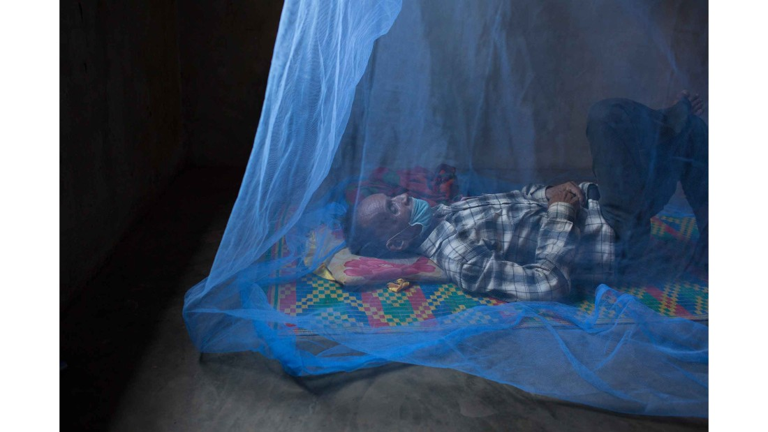 Sam Mowum, 71, takes a nap inside his home in Proy village in Mamot district, Cambodia. To avoid infecting his family, Sam Moeum left the family home to complete his treatment and now lives alone.