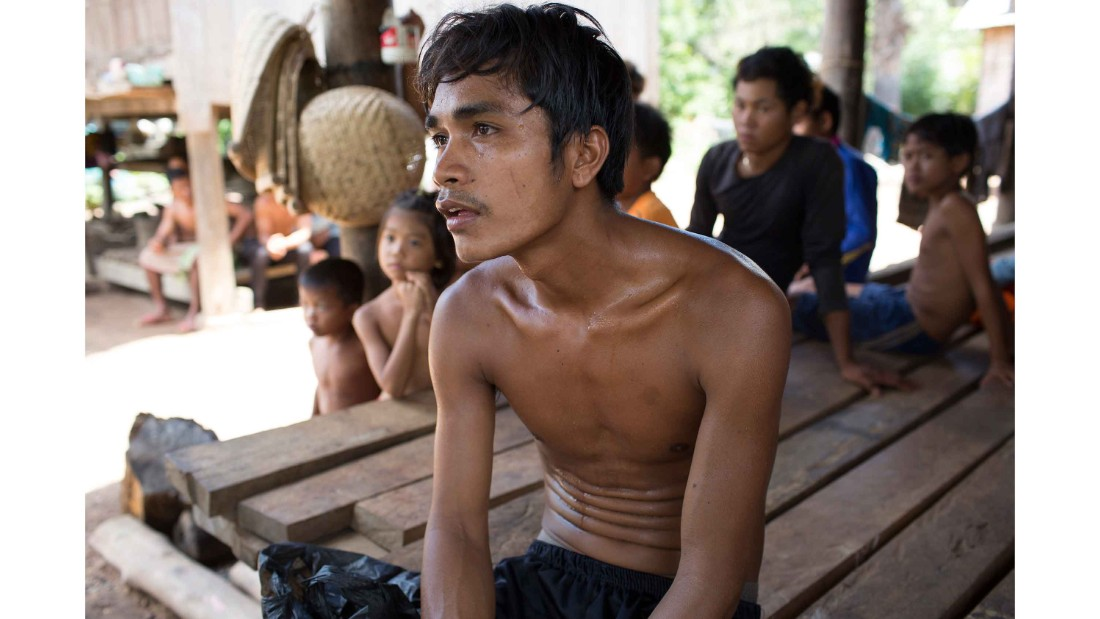 Pham Anyang, 28, stops for a portrait outside his home in Srosomthmy village, in Mamot district, Cambodia.  He is completing his TB treatment at home with the support of RHAC, a local NGO.
