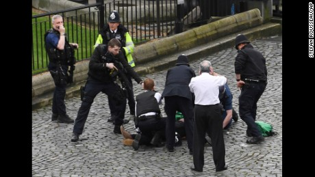 "A policeman points a gun at a man on the floor as emergency services attend the scene outside the Palace of Westminster, London, Wednesday, March 22, 2017.  London police say they are treating a gun and knife incident at Britain's Parliament ""as a terrorist incident until we know otherwise."" The Metropolitan Police says in a statement that the incident is ongoing. It is urging people to stay away from the area. Officials say a man with a knife attacked a police officer at Parliament and was shot by officers. Nearby, witnesses say a vehicle struck several people on the Westminster Bridge.  (Stefan Rousseau/PA via AP)."
