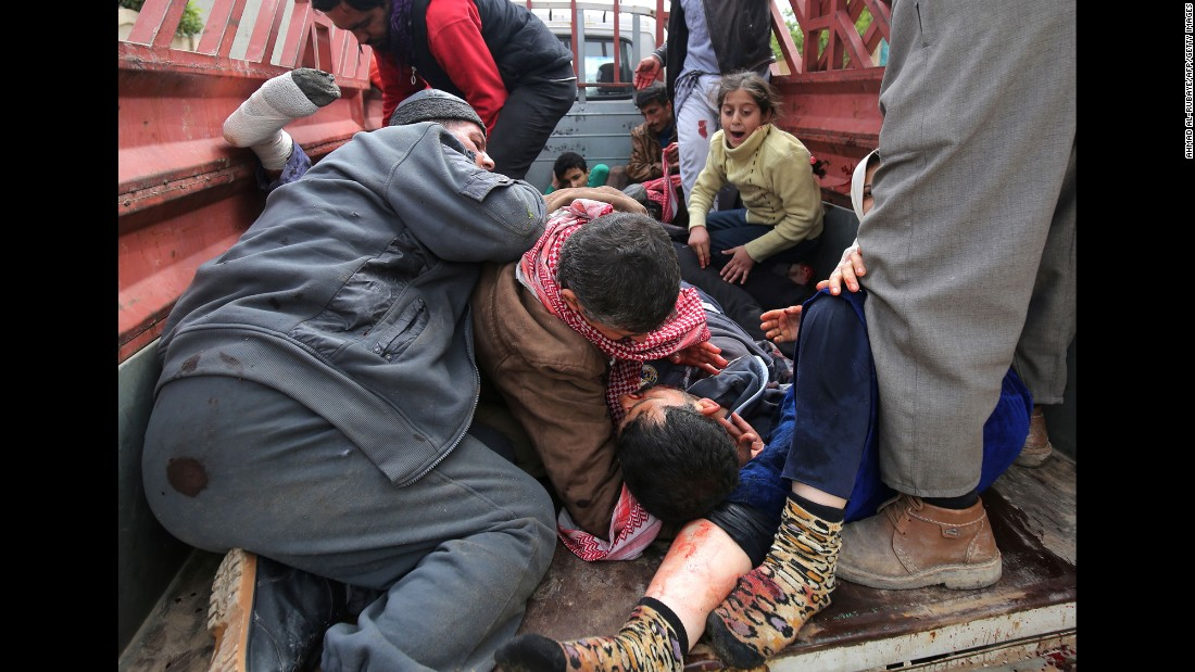 A girl reacts as a man hugs the body of her father after he was killed by an Islamic State mortar shell in the al Risala neighborhood of Mosul, Iraq, on Wednesday, March 22.
