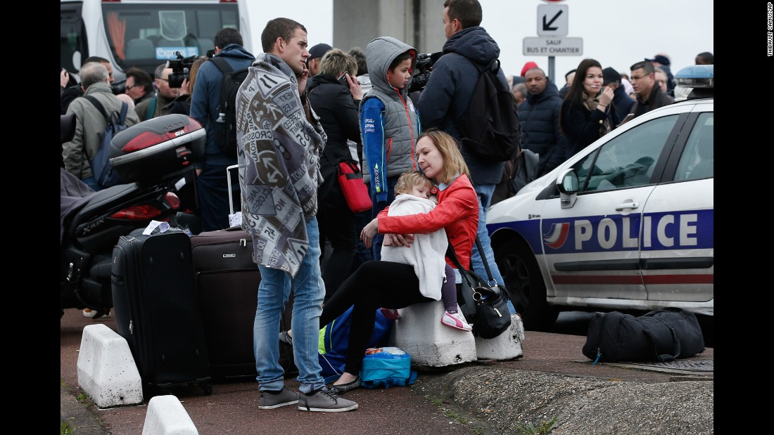 "Evacuated travelers wait outside the Orly Airport, south of Paris, on Saturday, March 18, after a suspect, <a href=""http://www.cnn.com/2017/03/18/europe/france-airport-evacuated-in-police-operation/"" target=""_blank"">identified by authorities as Ziyed Ben Belgacem</a>, held a gun on a French female soldier. Belgacem, who is also accused of shooting a police officer earlier in the day when he stole the officer's weapon, was shot and killed by security forces at the airport. Paris Prosecutor Francois Molins said French terrorism investigators will lead the inquiry into the attacks."