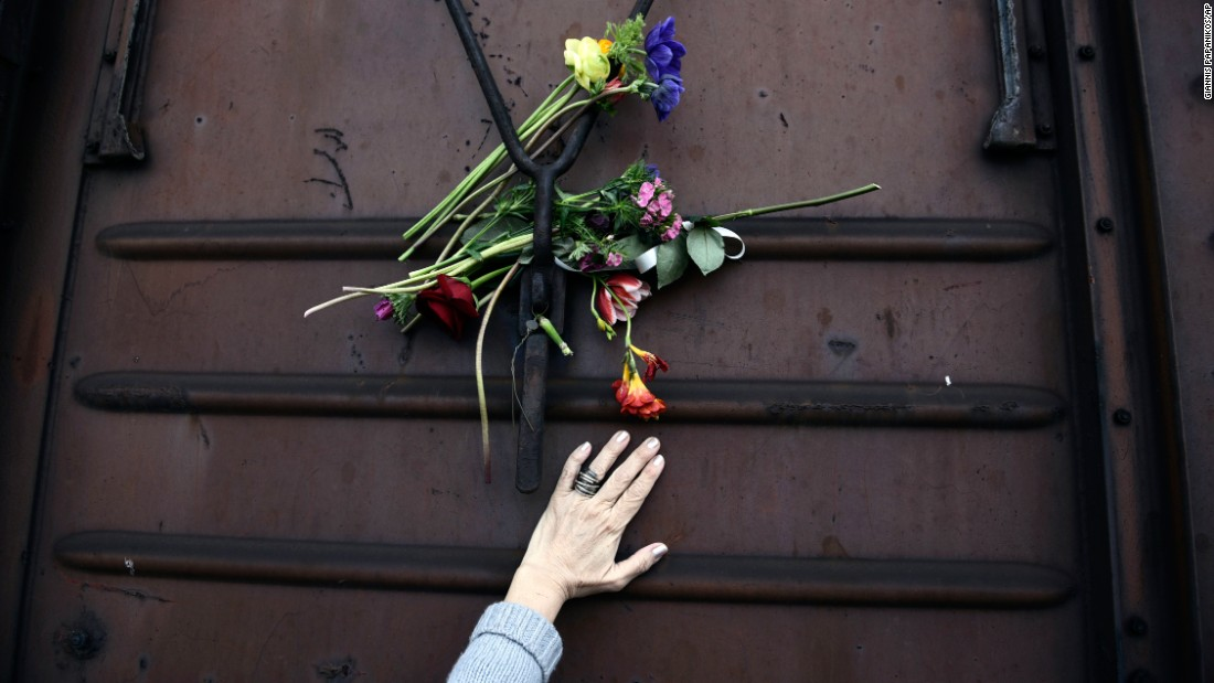 A woman places flowers on a train wagon at an old train station in Thessaloniki, Greece, on Sunday, March 19. Residents of the northern Greek city visited the station to mark the 74th anniversary of the roundup and deportation of Thessaloniki Jews to Nazi extermination camps during World War II.