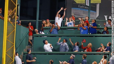 Fans in coveted Green Monster seats vying for a ball hit by Boston Red Sox player Mookie Betts during a practice session in 2016.