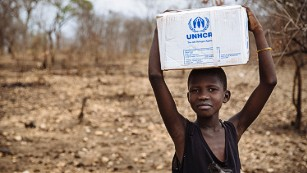 A South Sudanese refugee carries a relief box in Uganda.