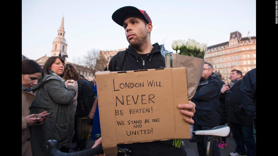 "Patrick Johnson holds a sign that reads, ""London will never be beaten! We stand as one and united!"" Johnson says his mother was caught up in the 7/7 bombings in 2005, the coordinated attacks on London's transport system that left 52 dead and more than 700 injured. ""This isn't going to defeat anyone,"" he said in a thick east London accent. ""We're strong."" ""7/7, that didn't break us. This won't either."""