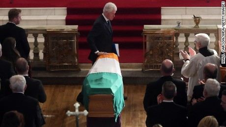 Before speaking to the gathered, former US President Bill Clinton touches the coffin of Northern Ireland's former Deputy First Minister and ex-IRA commander Martin McGuinness at St Columba's Church Long Tower on March 23, 2017 in Londonderry, Northern Ireland.