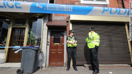 Police stand guard Thursday at the entrance to an apartment on Hagley Road in Birmingham.