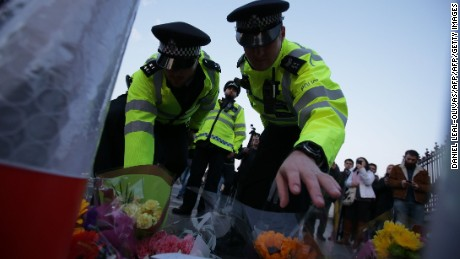 Police officers lay flowers in honour of the victims of the March 22 terror attack at the end of Westminster Bridge by the Houses of Parliament in central London on March 23, 2017 after the bridge reopened.  Britain's parliament reopened on Thursday with a minute's silence in a gesture of defiance a day after an attacker sowed terror in the heart of Westminster, killing three people before being shot dead. Sombre-looking lawmakers in a packed House of Commons chamber bowed their heads and police officers also marked the silence standing outside the headquarters of London's Metropolitan Police nearby.  / AFP PHOTO / Daniel LEAL-OLIVAS        (Photo credit should read DANIEL LEAL-OLIVAS/AFP/Getty Images)