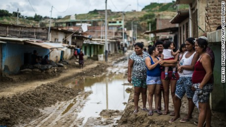 Local residents stand next to the muddy road after the flooding caused by recent rains, in the province of Paita in Piura, northern Peru, on March 24, 2017.  The El Nino climate phenomenon is causing muddy rivers to overflow along the entire Peruvian coast, isolating communities and neighbourhoods. / AFP PHOTO / Ernesto BENAVIDES        (Photo credit should read ERNESTO BENAVIDES/AFP/Getty Images)