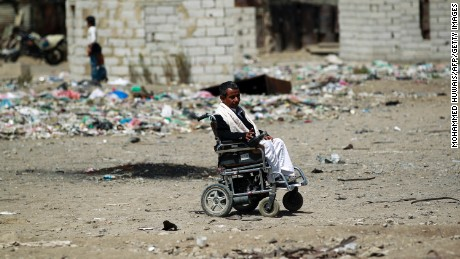 A Yemeni man in a wheelchair makes his way at a slum in Sanaa.