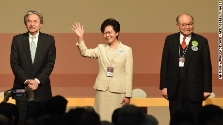 CORRECTION - Hong Kong's new chief executive Carrie Lam (C) waves while her defeated opponents Woo Kwok-hing (R) and John Tsang (L) look on after winning the Hong Kong chief executive election in Hong Kong on March 26, 2017. Beijing favourite Carrie Lam was selected as Hong Kong's new leader by a mainly pro-China committee, in an election dismissed as a sham by democracy activists who fear the loss of the city's cherished freedoms. / AFP PHOTO / Anthony WALLACE / The erroneous mention[s] appearing in the metadata of this photo by Anthony WALLACE has been modified in AFP systems in the following manner: [correcting positioning of John Tsang and Woo Kwok-hing]. Please immediately remove the erroneous mention[s] from all your online services and delete it (them) from your servers. If you have been authorized by AFP to distribute it (them) to third parties, please ensure that the same actions are carried out by them. Failure to promptly comply with these instructions will entail liability on your part for any continued or post notification usage. Therefore we thank you very much for all your attention and prompt action. We are sorry for the inconvenience this notification may cause and remain at your disposal for any further information you may require.        (Photo credit should read ANTHONY WALLACE/AFP/Getty Images)