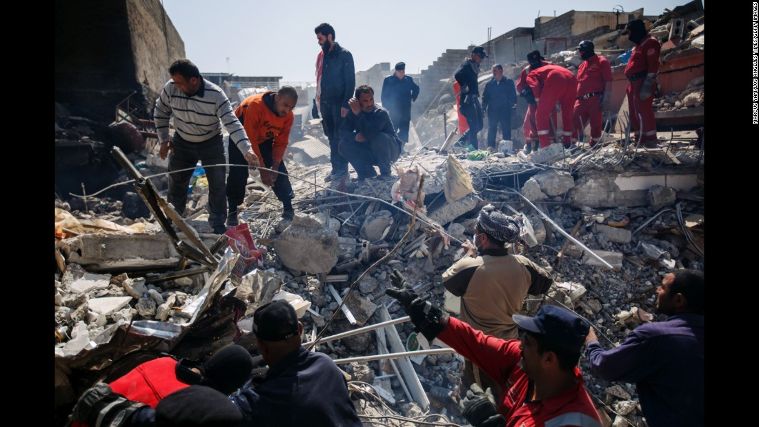 Residents help Iraqi civil defense force members recover corpses trapped in the rubble of a home destroyed by reported coalition airstrikes in the al Jadidah neighborhood of Mosul on March 24, 2017.