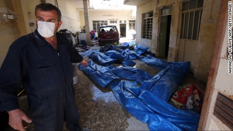 An Iraqi rescue worker gestures towards bodies wrapped in plastic in the Mosul al-Jadida area on March 26, 2017, following air strikes in which civilians have been reportedly killed during an ongoing offensive against the Islamic State group.   Iraq is investigating air strikes in west Mosul that reportedly killed large numbers of civilians in recent days, a military spokesman said.