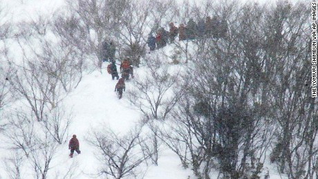 Rescue team members climb the mountain at Nasu Onsen Family Ski Resort.