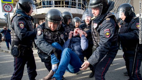 TOPSHOT - Riot police officers detain a protester during an unauthorised anti-corruption rally in central Moscow on March 26, 2017. Thousands of Russians demonstrated across the country on March 26 to protest at corruption, defying bans on rallies which were called by prominent Kremlin critic Alexei Navalny -- who was arrested along with scores of others. Navalny called for the protests after publishing a detailed report this month accusing Prime Minister Dmitry Medvedev of controlling a property empire through a shadowy network of non-profit organisations.   / AFP PHOTO / Alexander UTKIN        (Photo credit should read ALEXANDER UTKIN/AFP/Getty Images)