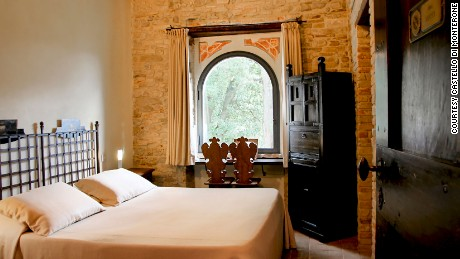 Castello di Monterone's rooms feature exposed stone walls and views over the Umbrian countryside.