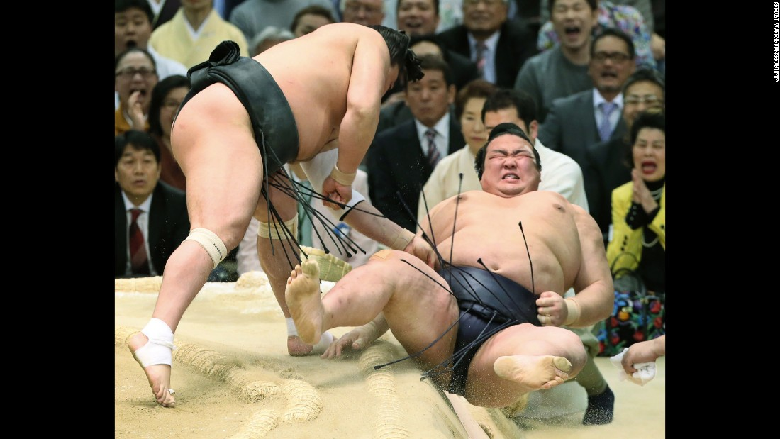 Japanese sumo wrestler Kisenosato is is thrown out of the ring by Harumafuji of Mongolia at the Spring Grand Sumo Tournament in Osaka, Japan, on Friday, March 24.