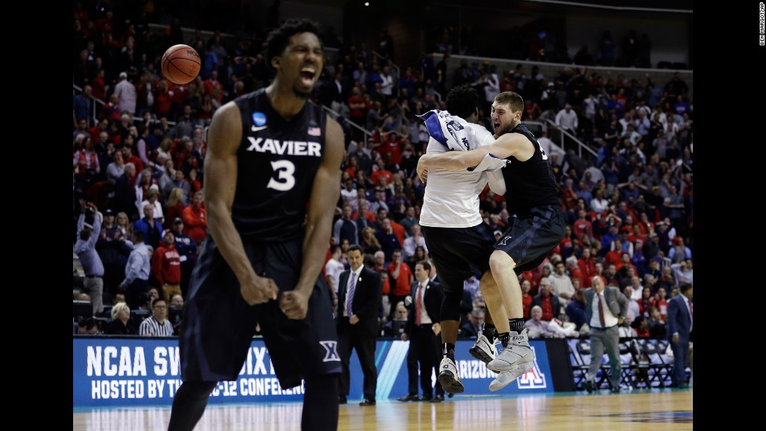 Xavier players Quentin Goodin, left, and Sean O'Mara, far right, celebrate after beating Arizona during an NCAA Tournament regional semifinal game Thursday, March 23. Gonzaga defeated Xavier on Saturday, March 25.