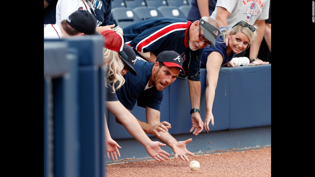 Fans reach over the wall for baseballs rolled to them by Atlanta Braves coaches before a spring training baseball game against the Washington Nationals on Tuesday, March 21, in West Palm Beach, Florida.
