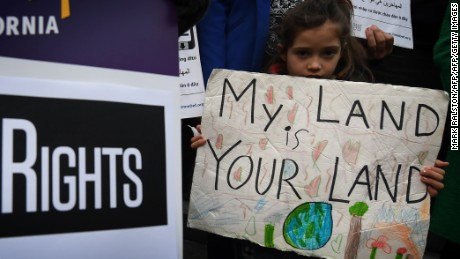 "Maya Casillas, 7, joins migrant rights group during a vigil to protest against US President Donald Trump's new crackdown on ""sanctuary cities"", outside the City Hall in Los Angeles on January 25, 2017. Some 300 such cities, counties or states -- from New York to Los Angeles -- exist throughout the United States, and many of them have vowed since Trump's election to protect the estimated 11 million undocumented migrants living in the country.  / AFP / Mark RALSTON        (Photo credit should read MARK RALSTON/AFP/Getty Images)"