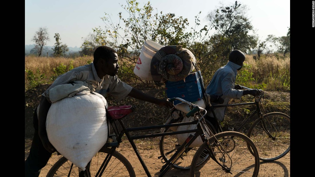 Two South Sudanese men push their bicycles after crossing the border. They've been on the road from Yet to Uganda for a month.