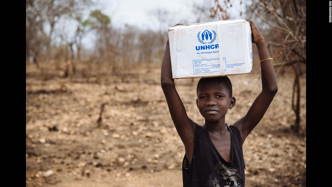 A South Sudanese refugee carrying a box of kitchen utensils, part of the Core Relief Items refugees are given at the recently established Imvepi settlement, Arua District, Northern Region, Uganda.
