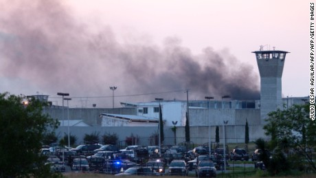 Smoke rises from Cadereyta prison where a brawl left several prisoners wounded on March 27, 2017 in Cadereyta, Nuevo Leon, Mexico.  / AFP PHOTO / Julio Cesar AGUILAR        (Photo credit should read JULIO CESAR AGUILAR/AFP/Getty Images)