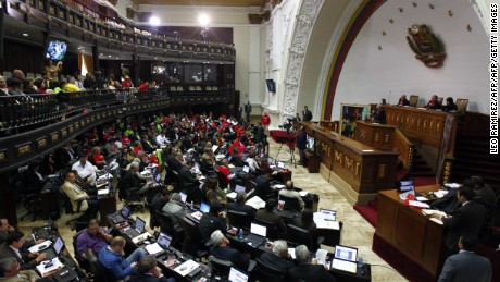 "Venezuela's National Assembly debates on a measure that would give Venezuelan President Nicolas Maduro extraordinary powers over the economy following a controversial attempt to forcibly cut consumer prices, at the parliament in Caracas, on November 14, 2013. Maduro's United Socialist Party of Venezuela (PSUV) had been one lawmaker short of the votes needed in the National Assembly to pass the measure, which needs a three-fifths majority. The party got the requisite 99th vote on November 13 by ousting opposition deputy Maria Mercedes Aranguren who was replaced by her alternate, Carlos Flores, considered a ""Chavista"", a follower of the doctrine of late leader Hugo Chavez, and who is expected to vote for the presidential ""enabling law.""   AFP PHOTO/Leo RAMIREZ        (Photo credit should read LEO RAMIREZ/AFP/Getty Images)"