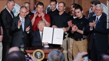 "President Donald Trump holds up the signed executive order ""Promoting Energy Independence and Economic Growth"" Tuesday, March 28, 2017, at EPA headquarters in Washington. (AP Photo/Pablo Martinez Monsivais)"