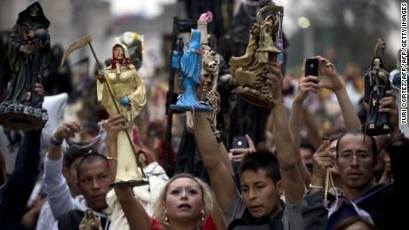 Devotees hold aloft their figures of Santa Muerte (Saint of Death) before the central altar asking for favors during the main celebration in the market of one of the most dangerous neighborhoods,  known as Tepito in Mexico City, on November 1, 2012. Santa Muerte is an occult figure venerated primarily in Mexico and the United States, probably a syncretism between Mesoamerican and Catholic beliefs, although strongly condemned by the Catholic Church as Satanic.  AFP PHOTO / YURI CORTEZ        (Photo credit should read YURI CORTEZ/AFP/Getty Images)