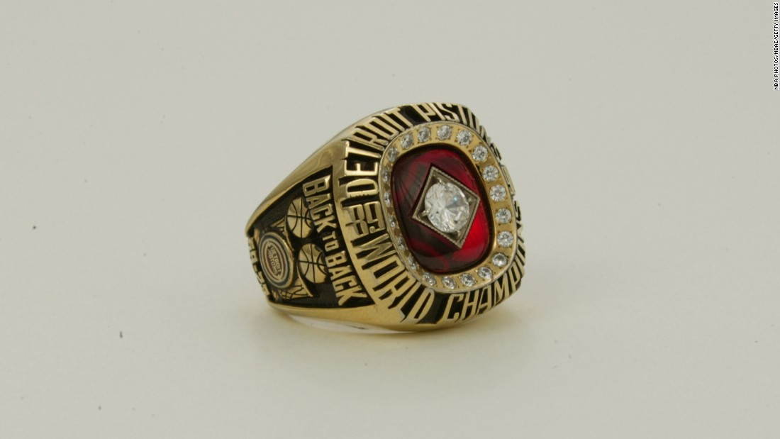 "The ring for the 1989-90 Detroit Pistons featured a large diamond surrounded by 20 smaller diamonds. On the side of the ring are the words ""back to back"" -- signifying the team's consecutive championships."