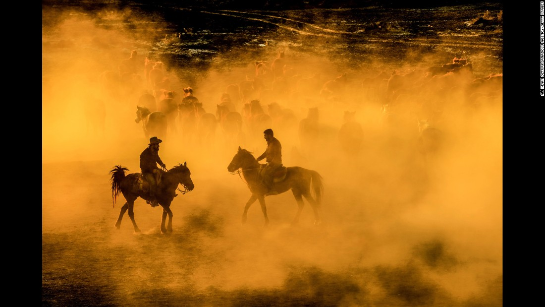 Men ride with a herd of horses Tuesday, March 28, at the foothills of Mount Erciyes in Kayseri, Turkey.