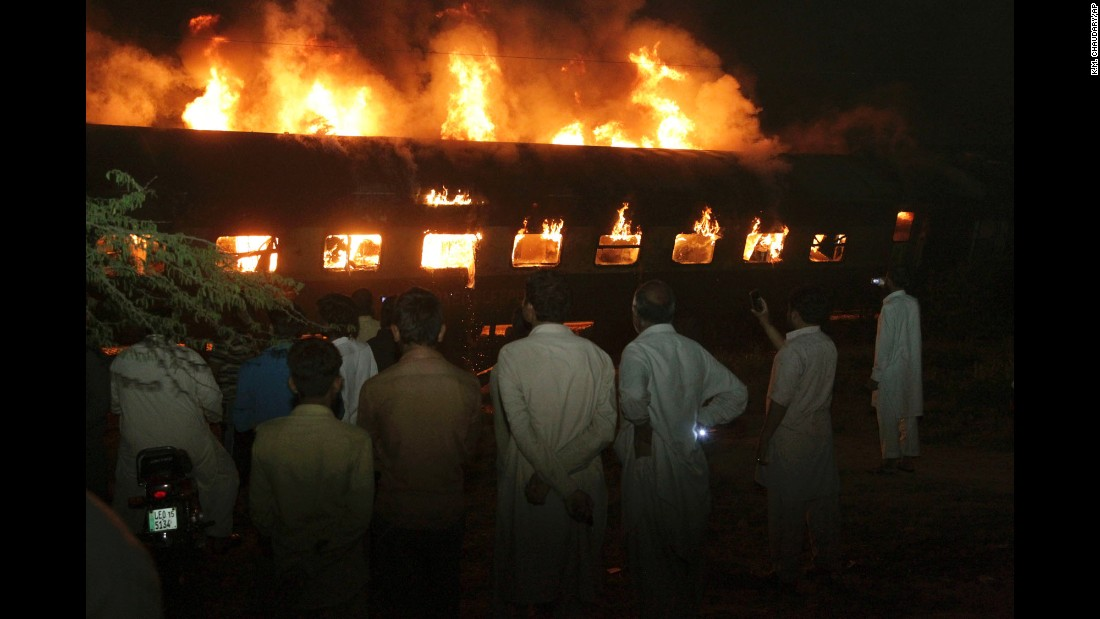 People look at a burning passenger train in Sheikhupura, Pakistan, on Tuesday, March 28. Authorities said the train collided with an oil-tanker truck, killing at least one person and injuring others.