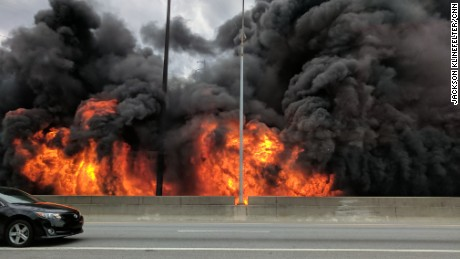 Flames rise Thursday evening along an elevated stretch of Interstate 85 north of downtown Atlanta.