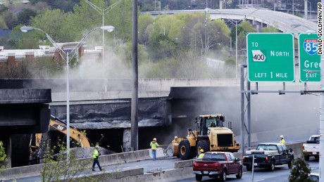 Crews work Friday on a section of an Interstate 85 overpass that collapsed during a masive fire.