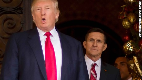 (FILES): This December 21, 2016 file photo shows US President-elect Donald Trump (L) with with Trump National Security Adviser designate Lt. General Michael Flynn (R) at Mar-a-Lago in Palm Beach, Florida.