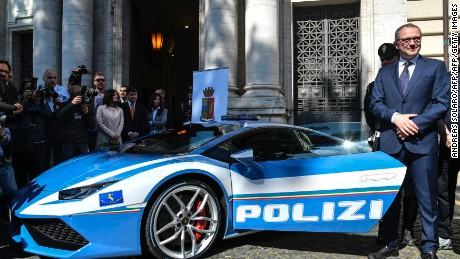 Lamborghini CEO Stefano Domenicali stands next to the police-liveried Huracan during its unveiling.