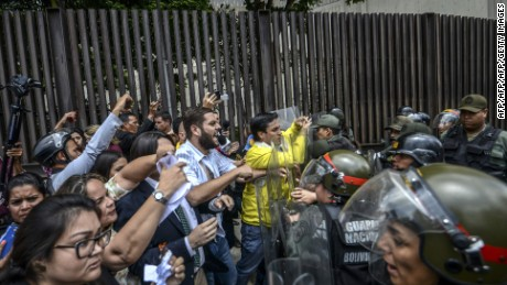 "Venezuelan opposition deputies Juan Requesen (C-L) and, Carlos Paparoni (yellow jacket) scuffle with National Guard personnel in riot gear during a protest in front of the Supreme Court in Caracas on March 30, 2017.  Venezuela's Supreme Court took over legislative powers Thursday from the opposition-majority National Assembly, whose speaker accused leftist President Nicolas Maduro of staging a ""coup."" / AFP PHOTO / JUAN  BARRETO        (Photo credit should read JUAN  BARRETO/AFP/Getty Images)"
