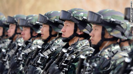 "This photo taken on February 27, 2017 shows Chinese military police attending an anti-terrorist oath-taking rally in Hetian, northwest China's Xinjiang Uygur Autonomous Region.  Islamic State militants from China's Uighur ethnic minority have vowed to return home and ""shed blood like rivers"", according to a jihadist-tracking firm, in what experts said marked the first IS threat against Chinese targets. / AFP PHOTO / STR / China OUT        (Photo credit should read STR/AFP/Getty Images)"