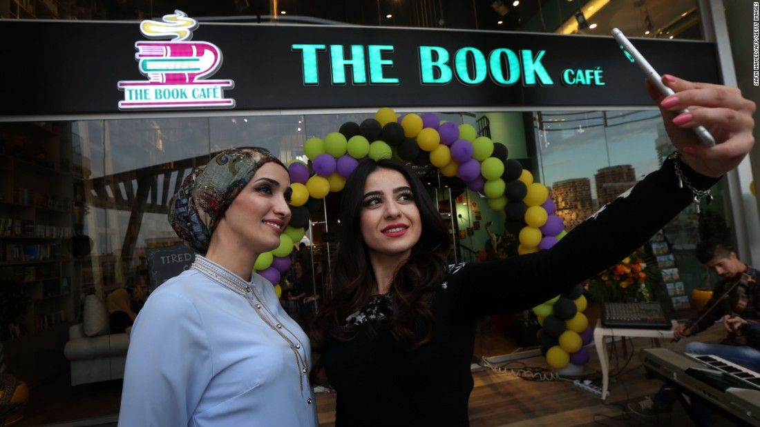 Women in Erbil, Iraq, pose for a selfie Friday, March 10, outside The Book Cafe, a book-selling coffee shop that is the first of its kind in the Kurdish region of Iraq.