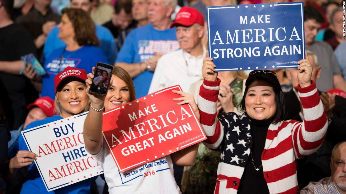 Supporters of US President Donald Trump take selfies and hold up signs during a rally in Louisville, Kentucky, on Monday, March 20.