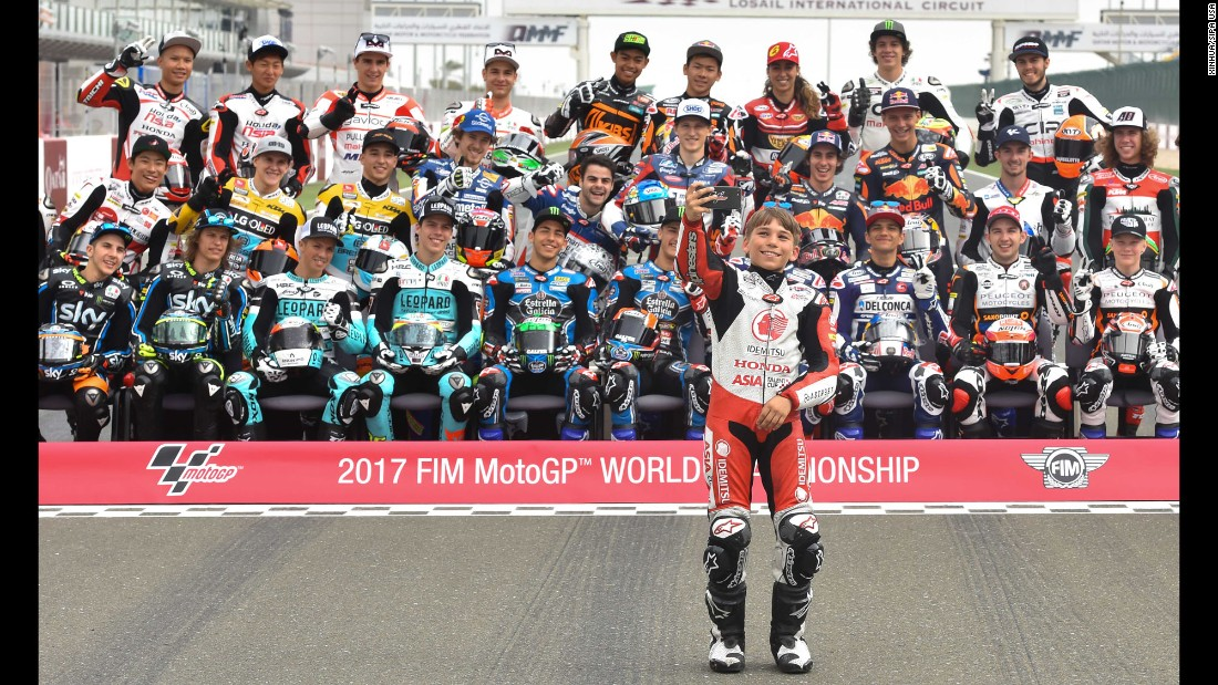 A boy takes a selfie with Moto3 riders before a practice session in Doha, Qatar, on Thursday, March 23.