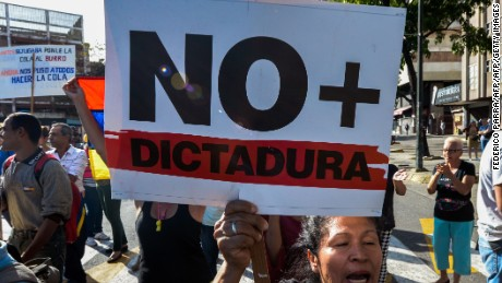 "A Venezuelan opposition activist, holds a sign reading ""No more dictatorship"" and chants slogans against the government of President Nicolas Maduro, during a march along a street of Caracas on March 31, 2017. Venezuela's Supreme Court took over legislative powers Thursday from the opposition-majority National Assembly, whose speaker accused leftist President Nicolas Maduro of staging a ""coup"". / AFP PHOTO / FEDERICO PARRA        (Photo credit should read FEDERICO PARRA/AFP/Getty Images)"