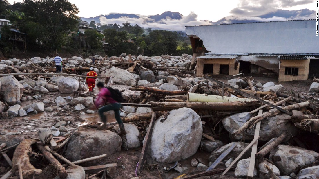 People walk through heaps of rubble left by the mudslides in Mocoa.