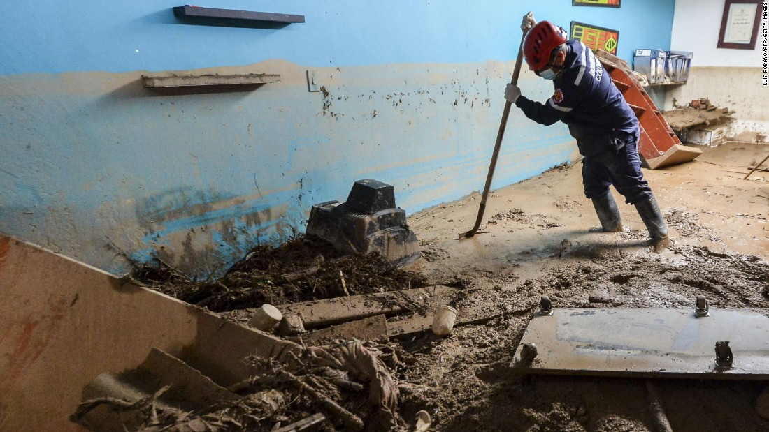 A fireman searches for victims inside a mud-swamped house.
