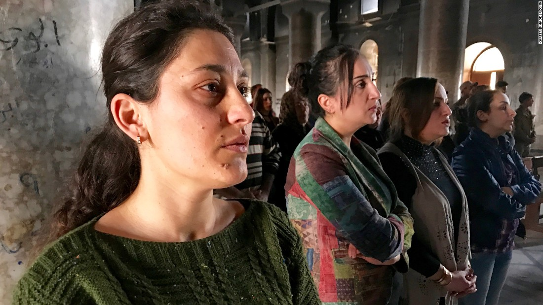 Women pray during a mass held at the church.  Many Qaraqosh residents return to the city during the day to take part in church services and check on their properties.