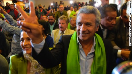 "The Ecuadorean presidential candidate of the ruling Alianza PAIS party, Lenin Moreno, gives the ""V for victory"" sign next to his wife Rocio Gonzalez (L) as they listen with supporters to the first results of the runoff election, in Quito on April 2, 2017. / AFP PHOTO / RODRIGO BUENDIA        (Photo credit should read RODRIGO BUENDIA/AFP/Getty Images)"